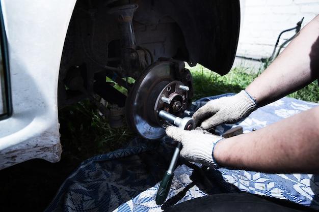 Naprawy samochodów. zmiana koła.kierowca zmienia koło w samochodzie