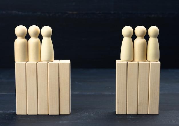 Naprzeciw siebie stoją grupy drewnianych postaci mężczyzn. koncepcja konfliktu interesów, budowanie dialogu, rozwiązania kompromisowe