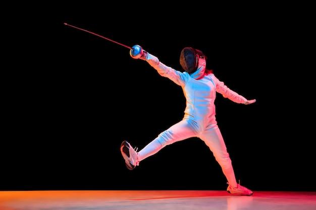 Naprzód. teen dziewczyna w stroju szermierki z mieczem w ręku na białym na czarnym tle, neon light. młoda modelka ćwicząca i trenująca w ruchu, w działaniu. copyspace. sport, młodość, zdrowy tryb życia.