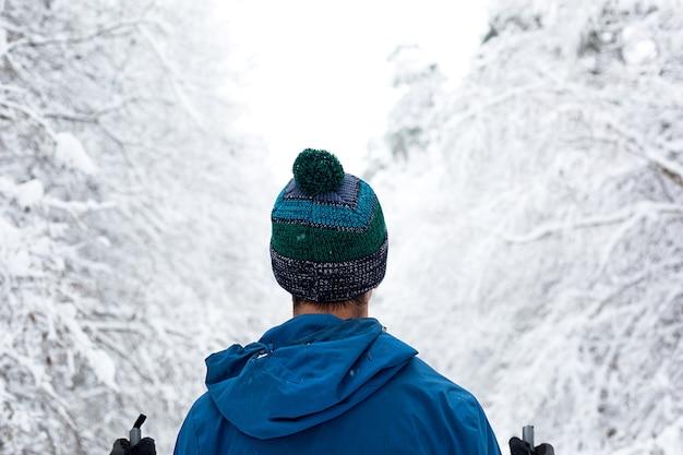 Narciarstwo biegowe w zimowym lesie, narciarz w czapce z pomponem z kijkami