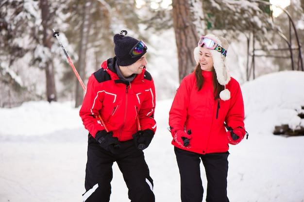 Narciarstwo, śnieg, zimowe zabawy, szczęśliwa rodzina jeździ na nartach w lesie.