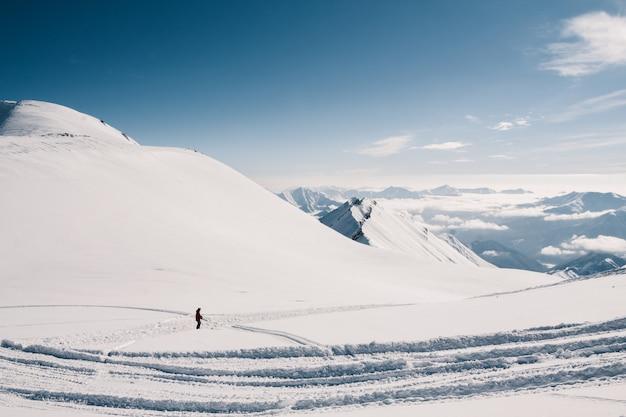 Narciarz jeździ na nartach ze szczytu góry w piękny słoneczny dzień. kaukaz w zimie, gruzja, region gudauri, mt. kudebi.