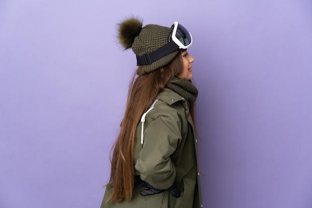 Narciarz kaukaski dziewczyna w okularach snowboardowych na białym tle na fioletowej ścianie cierpi na bóle pleców za wysiłek