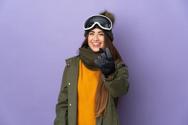 Narciarz kaukaski dziewczyna z okulary snowboardowe na białym tle