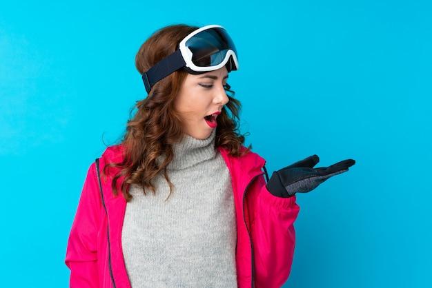Narciarz kobieta w okularach snowboardowych na pojedyncze niebieskie ściany gospodarstwa copyspace wyobraźni na dłoni