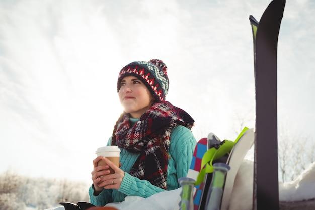 Narciarz kobieta z filiżanką kawy patrząc w górę i uśmiechnięty
