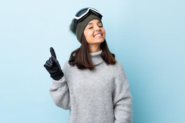 Narciarz mieszanej rasy kobieta w okularach snowboardowych na pojedyncze niebieskie miejsce, pokazując i podnosząc palec na znak najlepszych