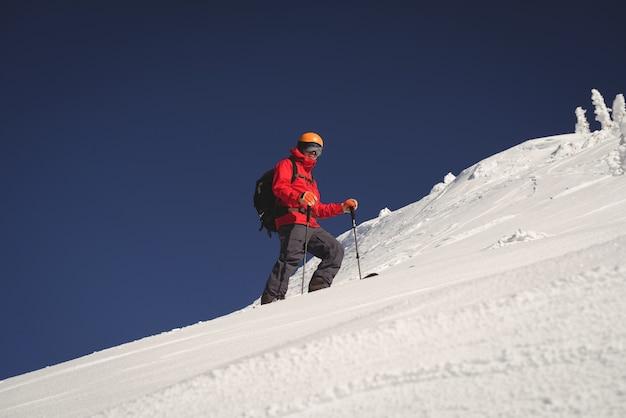 Narciarz na nartach w zaśnieżonych alpach
