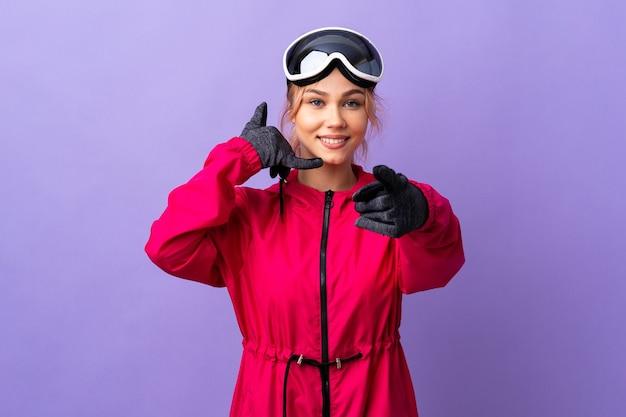 Narciarz nastolatek dziewczyna w okularach snowboardowych na białym tle fioletowy telefon robi gest i wskazuje przód