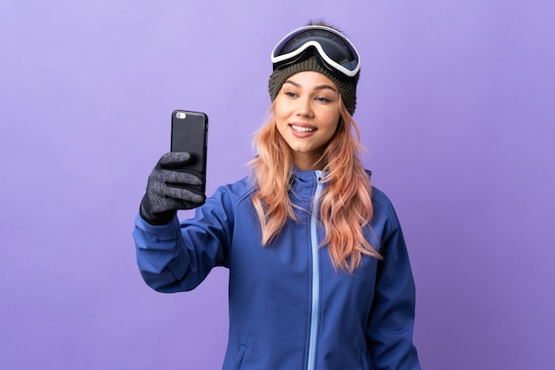 Narciarz nastolatek dziewczyna w okularach snowboardowych na odosobnionej fioletowej ścianie dokonywanie selfie