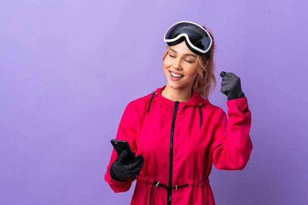 Narciarz nastolatek dziewczyna w okularach snowboardowych na odosobnionej fioletowej ścianie z telefonem w pozycji zwycięstwa