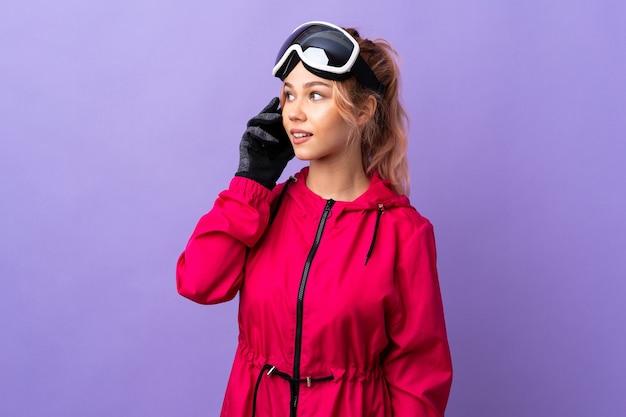 Narciarz nastolatek dziewczyna w okularach snowboardowych na odosobnionym fioletowym prowadzeniu rozmowy z kimś przez telefon komórkowy