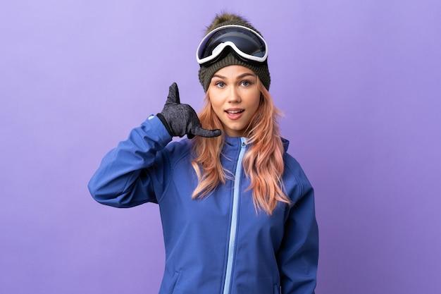 Narciarz nastolatek dziewczyna w okularach snowboardu na odosobnionej fioletowej ścianie dokonywanie gestu telefonu. oddzwoń do mnie znak