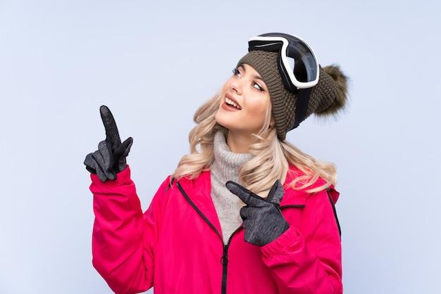 Narciarz nastolatka dziewczyna w okularach snowboardowych na białym tle niebieski wskazując palcem wskazującym, świetny pomysł