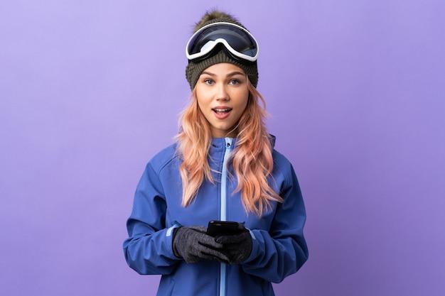 Narciarz nastolatka dziewczyna w okularach snowboardowych na odosobnionym fioletowym tle zaskoczony i wysyłający wiadomość