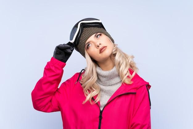 Narciarz nastolatka dziewczyna w okularach snowboardowych na pojedyncze niebieskie ma wątpliwości i mylić wyraz twarzy