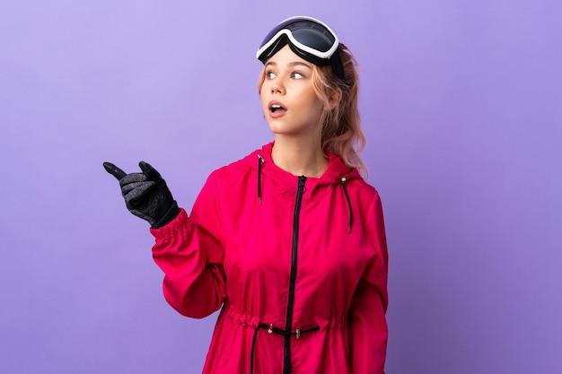 Narciarz nastolatka dziewczyna w okularach snowboardowych nad odosobnioną fioletową ścianą, która zamierza wykonać rozwiązanie, podnosząc palec