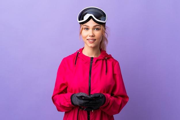 Narciarz nastolatka dziewczyna w okularach snowboardowych nad odosobnioną fioletową ścianą wysyłanie wiadomości z telefonu komórkowego