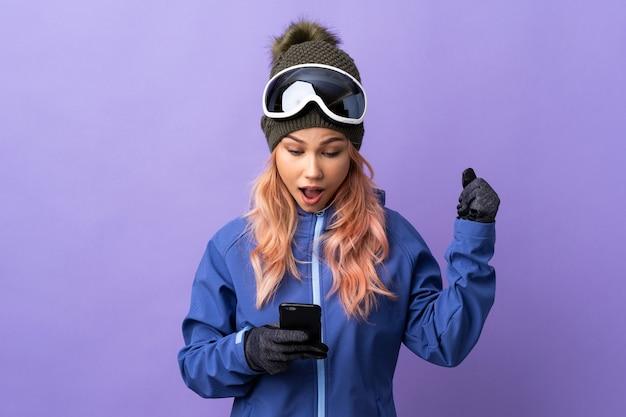 Narciarz nastolatka dziewczyna w okularach snowboardowych nad odosobnioną fioletową ścianą zaskoczony i wysyłający wiadomość