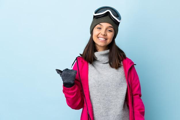 Narciarz rasy mieszanej kobieta w okularach snowboardowych na pojedyncze niebieskie miejsce, wskazując na bok, aby przedstawić produkt