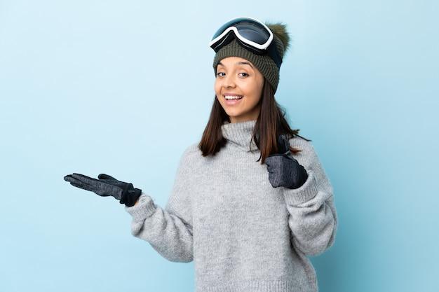 Narciarz rasy mieszanej z okularami snowboardowymi na niebieskiej ścianie, trzymając puste miejsce na dłoni, aby wstawić reklamę i kciuki do góry