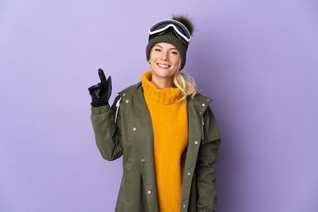 Narciarz rosjanka w okularach snowboardowych na białym tle na fioletowym tle pokazująca i unosząca palec na znak najlepszych