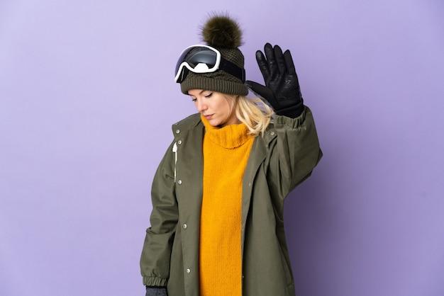Narciarz rosyjska dziewczyna w okularach snowboardowych na fioletowym tle robiąca gest zatrzymania i rozczarowana