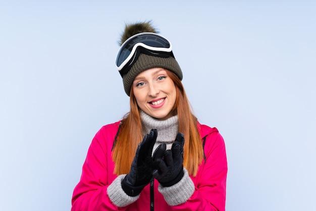 Narciarz ruda kobieta w okularach snowboardowych na pojedyncze oklaskiwane niebieskie ściany
