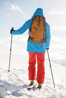 Narciarz spacerujący po stoku z nartą