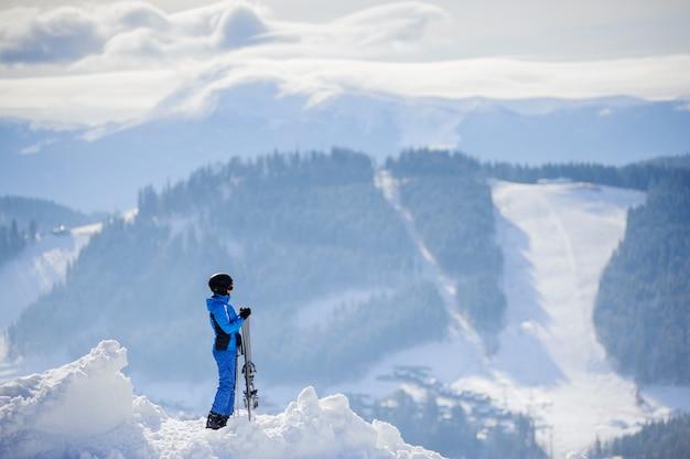 Narciarz stoi na szczycie góry i cieszyć się widokiem na piękne zimowe góry w słoneczny dzień