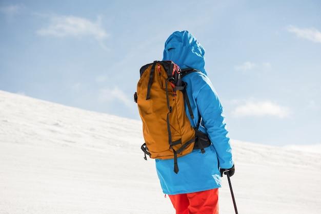 Narciarz stojący z nartami w ośnieżonych górach