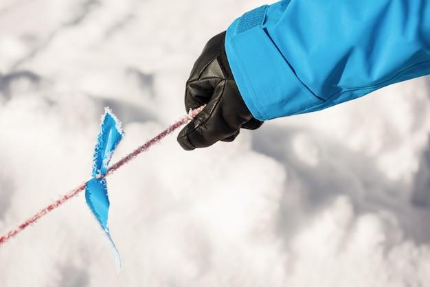 Narciarz trzyma słup w śniegu