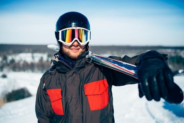 Narciarz trzyma w rękach narty i kijki