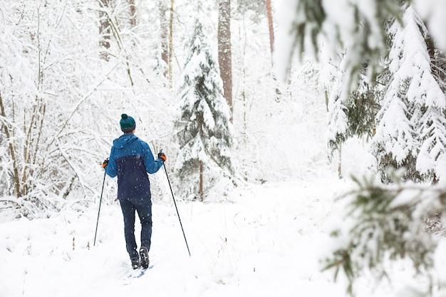 Narciarz w czapce z pomponem z kijkami narciarskimi w zaśnieżonym lesie. biegi narciarskie