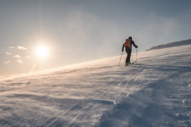 Narciarz z plecakiem wędrującym po śnieżnym wzgórzu w zamieci o zachodzie słońca