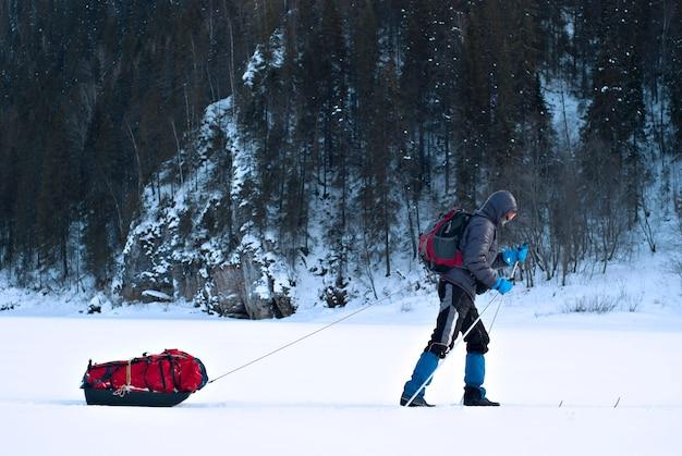 Narciarz z saniami towarowymi idący wzdłuż zamarzniętej rzeki na skalistym, zalesionym brzegu