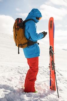 Narciarz za pomocą telefonu komórkowego w zaśnieżonych górach