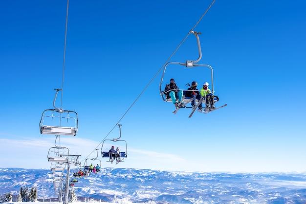 Narciarze na wyciągu narciarskim w górskim ośrodku z niebem i górami