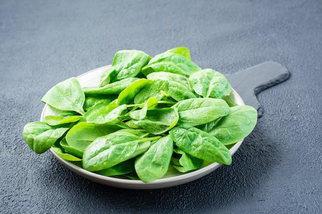 Naręcze świeżych liści szpinaku dla dzieci w kroplach wody na talerzu na tablicy łupkowej. jedzenie wegetariańskie, wellness i detoksykacyjne