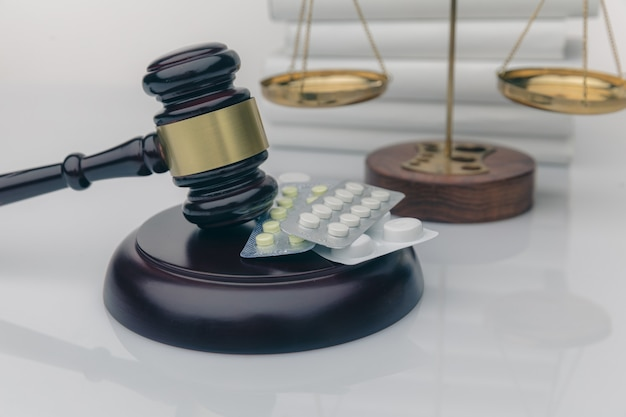Narkotyki i prawo. sędzia młotek i kolorowe pigułki na drewnianym biurku, ciemne tło, widok zbliżenie.