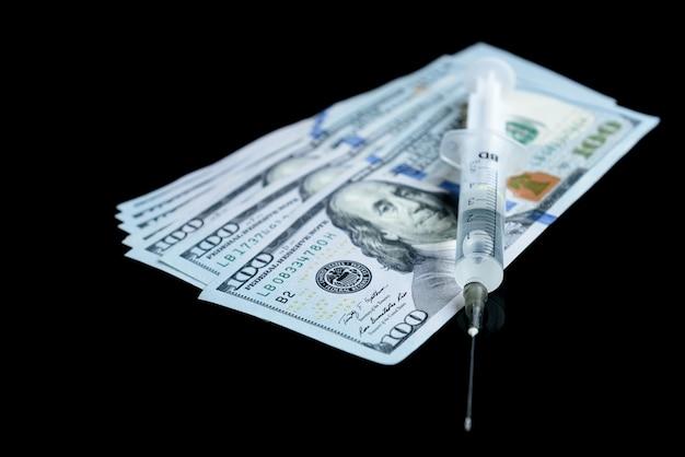 Narkotykowa heroina, strzykawki, pigułki i dolarowe pieniądze na czarnym stole.