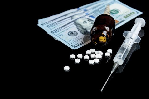 Narkotykowa heroina, strzykawki, pigułki i dolary na czarnym stole.