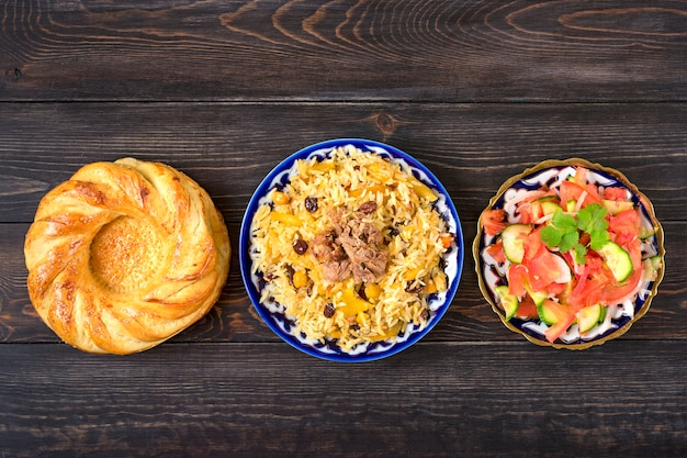 Narodowy uzbecki pilaw z mięsem, sałatka achichuk z pomidorów, ogórka, cebuli w talerzu z tradycyjnym