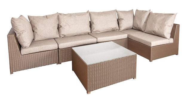 Narożna sofa i stolik na białym tle. wiklinowe meble rattanowe do ogrodu lub salonu.