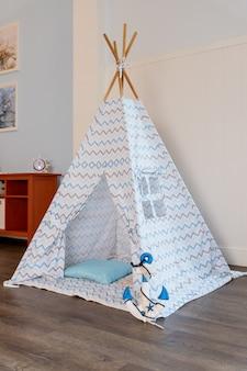 Narożnik pokoju dziecięcego z pięknie urządzonym namiotem do zabawy tipi i poduszkami. przytulny namiot do zabawy dla dzieci jako element wnętrza pokoju dziecięcego. wigwam dziecięcy. przytulna chatka z dekoracyjnym wystrojem w stylu boho.