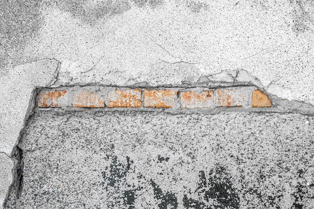 Narożny element tła zniszczonej ściany z pęknięciami i rysami.