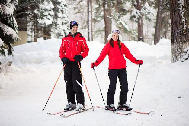 Narty, śnieg, zimowe szaleństwo, szczęśliwa rodzina jeździ na nartach w lesie.