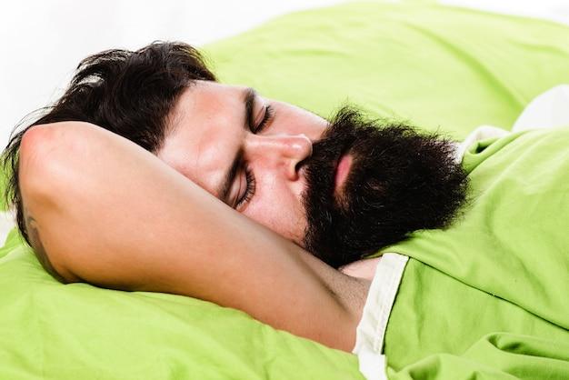 Naruszenia snu i czuwania. młody człowiek śpi na miękkich poduszkach w łóżku w domu. brodaty mężczyzna