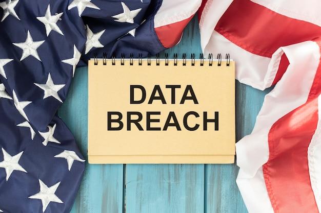 Naruszenie danych tekstowych w notatniku na tle flagi amerykańskiej