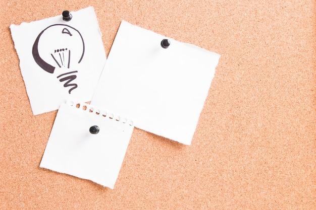 Narysowana żarówka na białym prześcieradle przymocowana do tablicy korkowej za pomocą szpilki z innymi papierami